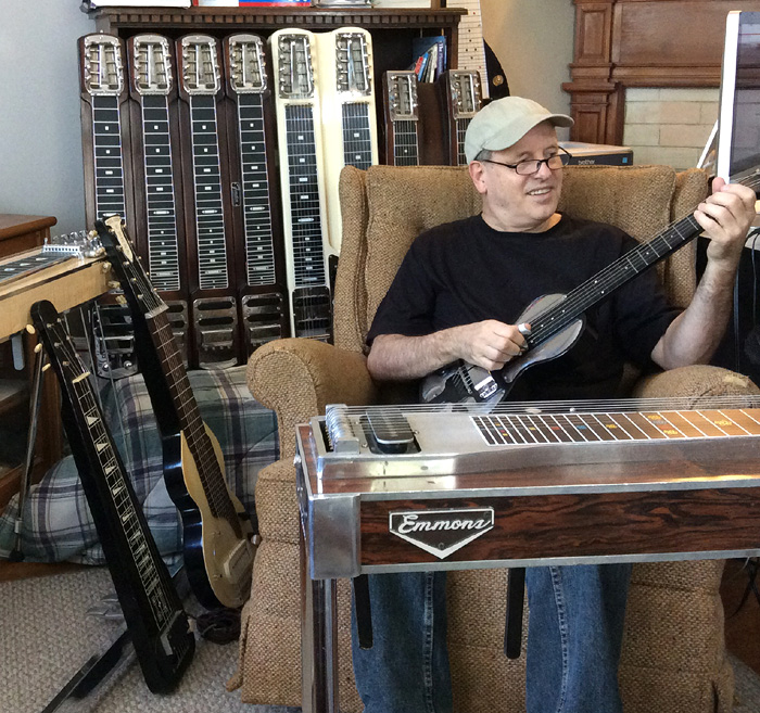 A picture of Doug Beaumier sitting down playing a steel guitar